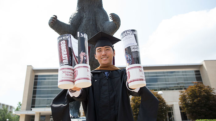 Graduating student holding posted by the bear statue.